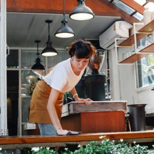 woman-cleaning-top-of-counter-in-cafe-with-cloth